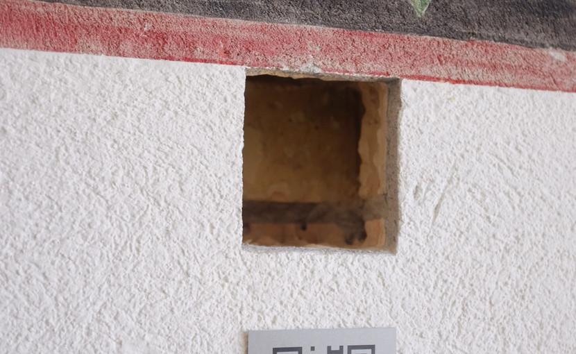 Die Sondierungsbohrung ist ca. 10 cm tief und legt den Aufbau und die Struktur der Wand frei, auf die das Alphabet aufgetragen wurde. Neben der Sondierungsbohrung verweist nun ein QR-Code auf diese Webseite. (Foto: Vera Ryser)