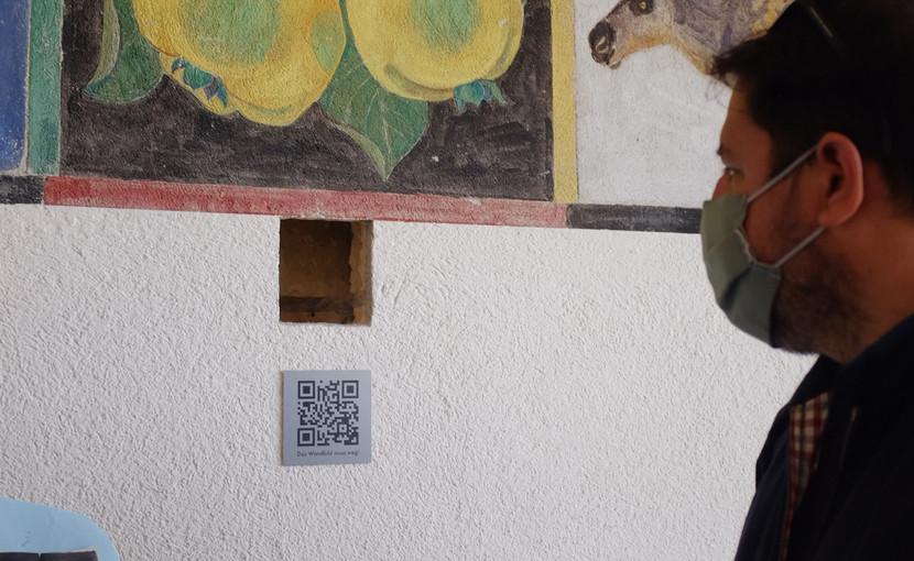Das Loch der Sondierungsbohrung bleibt bis auf Weiteres offen und verweist neben dem QR-Code auf das Projekt «Das Wandbild muss weg!». (Foto: Vera Ryser)