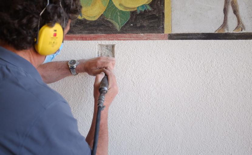 Tobias Hotz (Konservator / Restaurator) nimmt eine  erste Sondierungsbohrung neben dem Wandbild vor. (Foto: Vera Ryser)