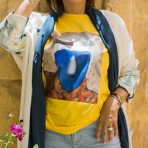 """Front view of a woman wearing yellow t-shirt with picture of the painting """"Anomalies"""" portrait of a man"""