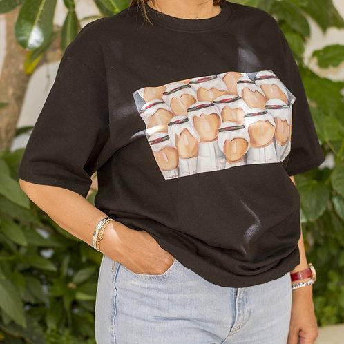 """Woman wearing black t-shirt with detail of the painting """"Al Rajajeel"""" representing group of Saudi men"""