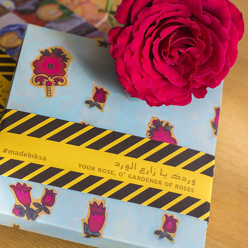 Cardboard gift box decorated with red flowers, secured with a black and yellow band, red rose