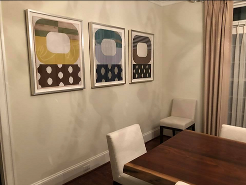 Contemporary geometric abstract paintings by Kazaan Viveiros installed in client's dining room