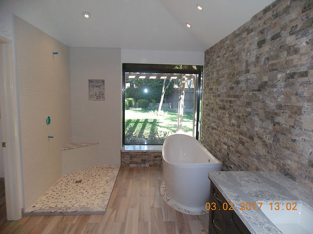 Bathroom with shower, bathtub and vanity with stone wall.