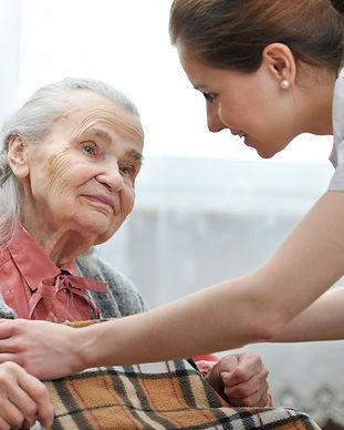 young-nurse-blanketing-elderly-lady.jpg