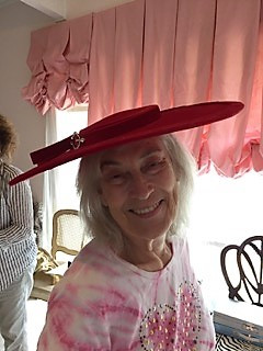 beautiful elderly smiling customer in large brimmed red hat