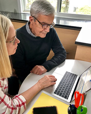 Nancy Goldsholl working on laptop with a gentleman