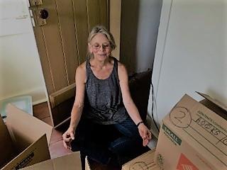 satisfied customer meditating among boxes