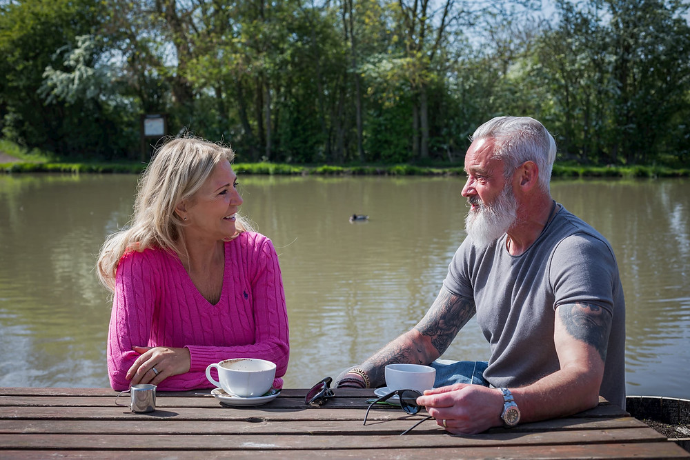 Older couple enjoying a coffee sitting at a canal side cafe.