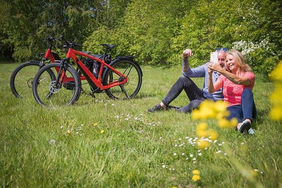 2 electric bikes and couple sitting in meadow enjoying a rest on the EBike holiday.