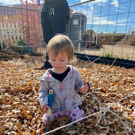 The kids dig the leaves and compost into the soil in preparation to plant in the spring.