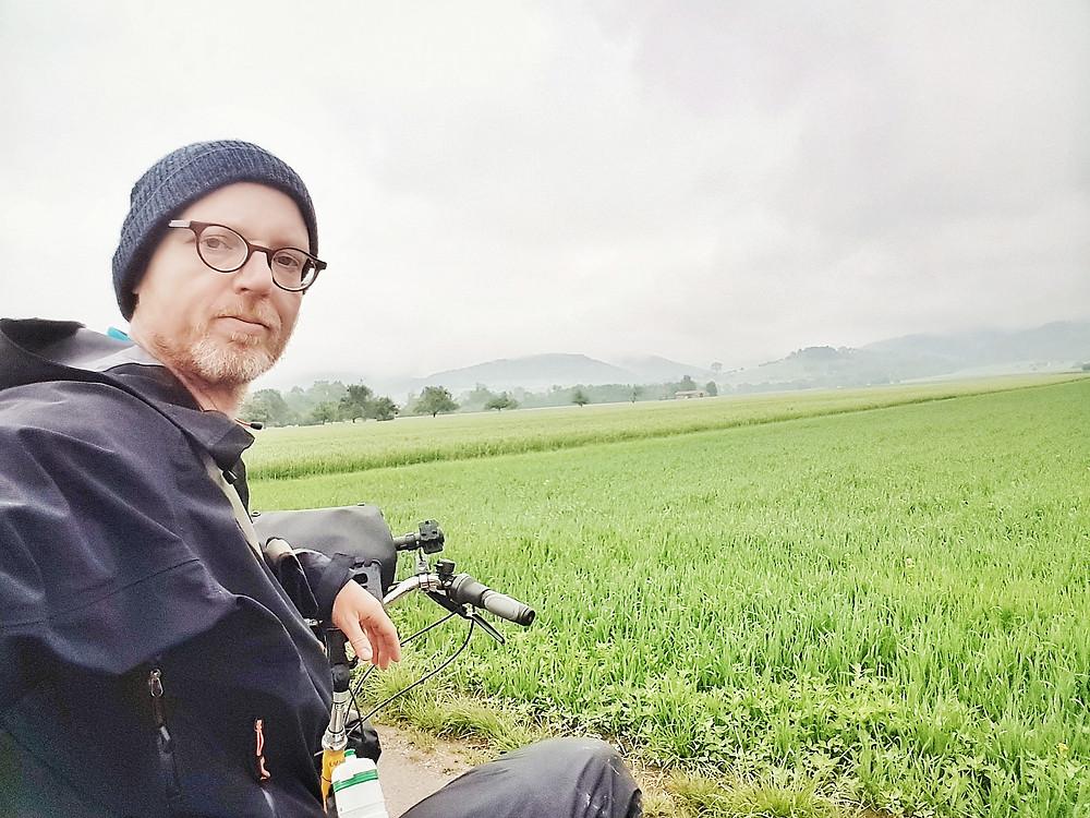 Ein Selbstporträt vor den Hügeln der Schwäbischen Alb. Im Vordergrund eine saftige Wiese. Die Hügel selbst sind im Dunst nur zu erahnen. Ich hocke noch halb auf dem Rad und versuche mich und diese grandiose Natur einzufangen.