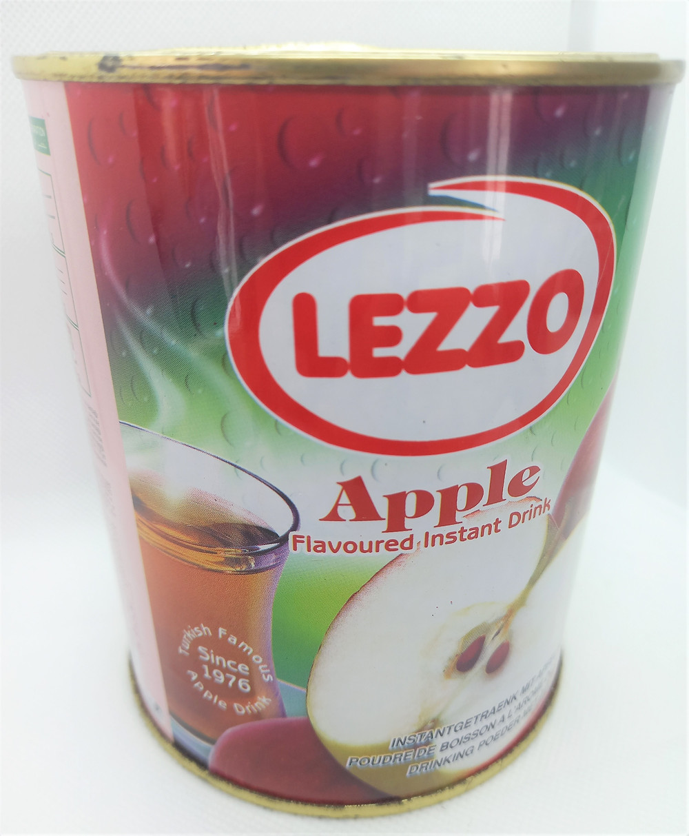 """A tin with the image of an apple and cup of tea on it, and the bold label """"LEZZO""""."""