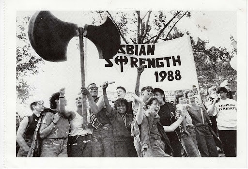 People celebrating around a Lesbian Strength 1988 sign and giant labrys