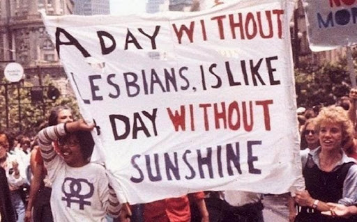 """At a march people holding a sign: """"A day without lesbians is like a day without sunshine"""""""