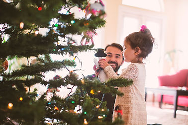 Pai e filha que decora a árvore de Natal