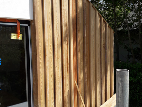 SiOO:X treated wood cladding to accelerate the aging process is being installed on site