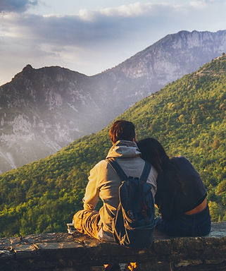 couples-sitting-in-while-facing-mountain