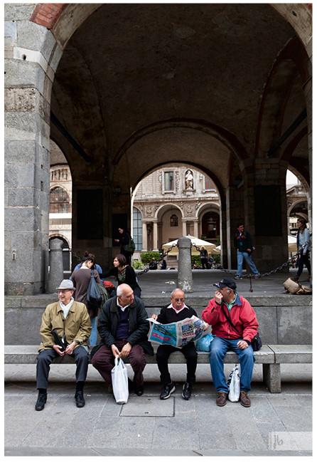 Männer in einer Reihe auf einer Bank, Mailand, Italien
