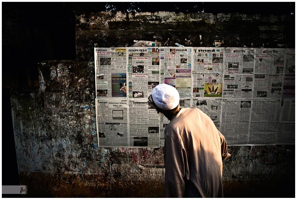 Salz auf Reisen, alter Mann liest öffentliche Zeitung an der Wand, Zeitunglesen in Dhaka, Bangladesch