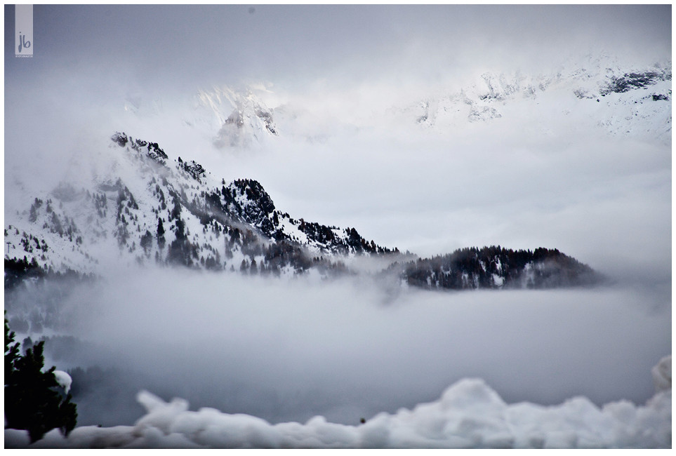 Berge in Schnee und Nebel, Alpen, über den Wolken