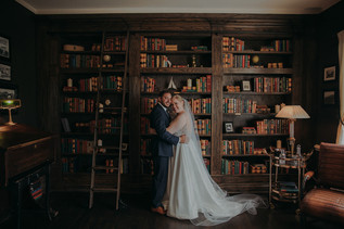 a bride and groom embrace in front of a bookshelf