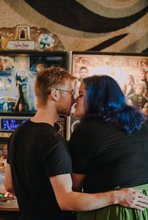 A man and women kiss in front of arcade games at I/O Arcade Bar in Madison Wisconsin