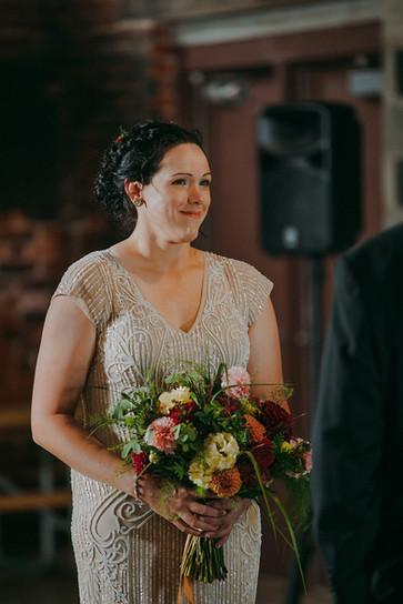 Bride smiles in during industrial wedding ceremony