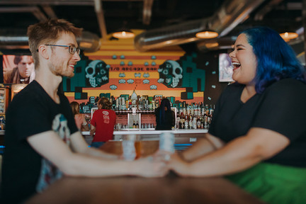 A man and women laugh while holding hands at I/O Arcade Bar in Madison Wisconsin