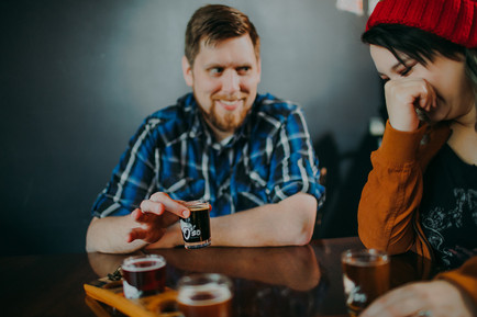 A man holds a shot glass inside O'so Brewing Company