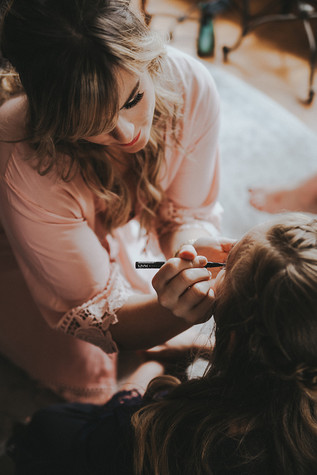 A women applies makeup to another at The Manor House during a southern Colorado foothills wedding.
