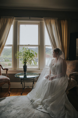 A bride covered in her veil sits on chair by the window at The Manor House
