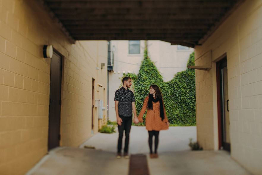 a man and women smile at each other as they walk through an alley in Downtown Stevens Point