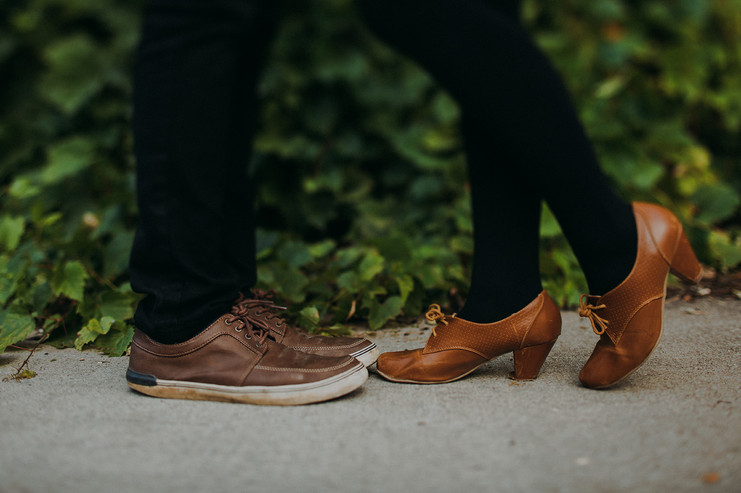 A mans brown leather shoes face a women's brown leather heels
