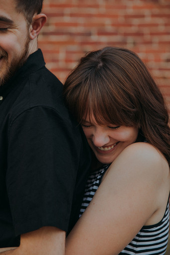 A women smiling as she hugs a man in in Downtown Stevens Point