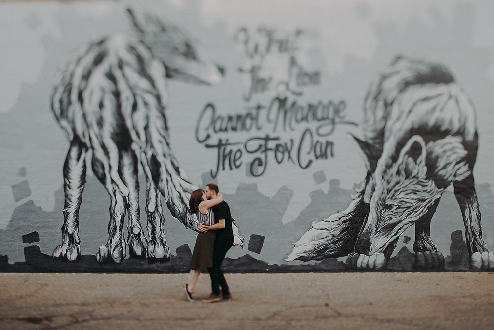 A man and women embrace in front of Alexander Landerman's mural in Downtown Stevens Point