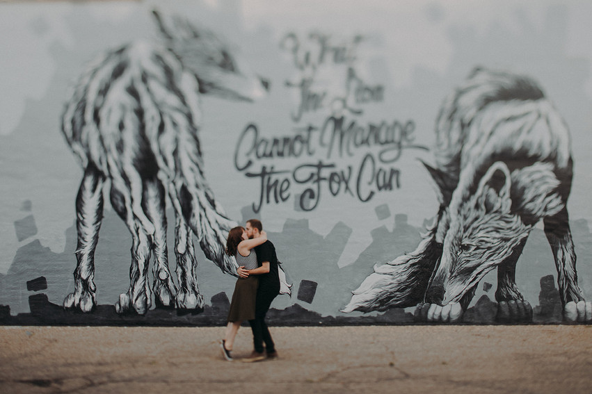 A man and women embrace in a kiss in front of Alexander Landermans mural in in Downtown Stevens Point