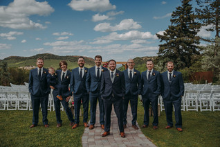 The groom and groomsman stand together and smile
