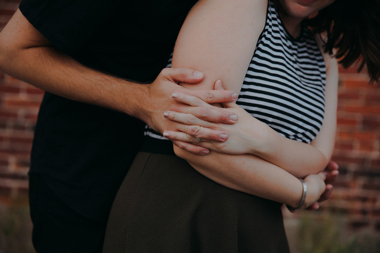 a close up of a man and women interlocking fingers in an embrace in Downtown Stevens Point