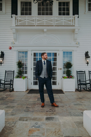 A man dressed in a navy suit and tie at The Manor House for a southern Colorado foothills wedding