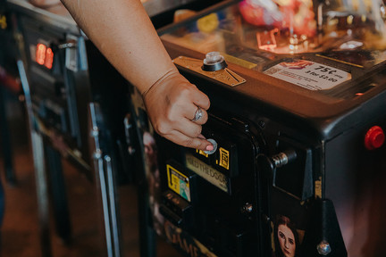 A woman puts a quarter into an arcade game at at I/O Arcade Bar in Madison Wisconsin