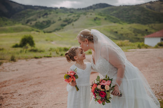 A brides kiss the forehead of a flower girl