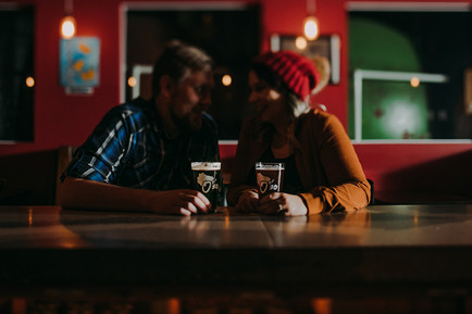 A man and woman sit at a the bar inside O'so Brewing Company