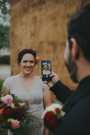 Groom snaps a photo of bride in Stevens Point, WI