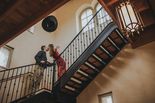 Man and women kiss in the staircase of the Villa Bellezza.