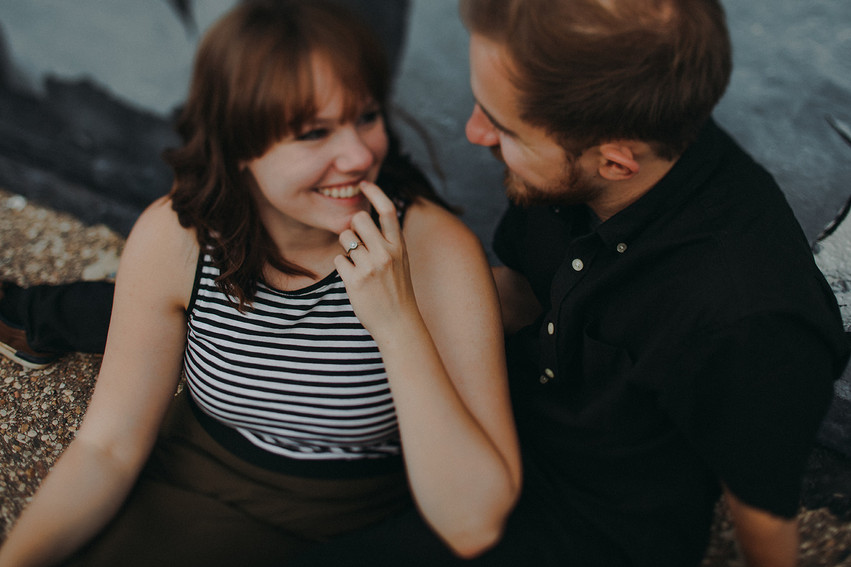A women giggles while staring at a man