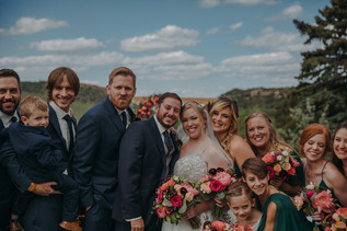 The bridal party smiles and huddles together at The Manor House during a southern Colorado foothills wedding.