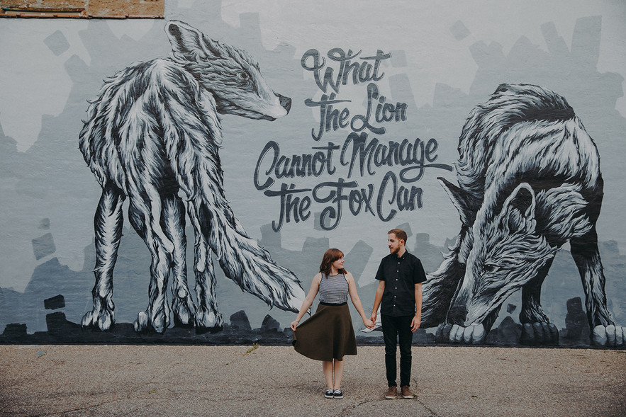 a man and women pose in front of Alexander Landermans mural in Downtown Stevens Point