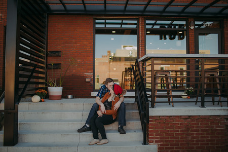 Man and women laugh on stairs in Downtown Stevens Point, outside of Ruby Coffee Roasters