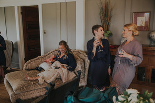 Three women enjoying drinks and each other company  The Manor House during a southern Colorado foothills wedding.